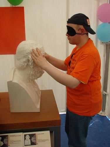 Esplorazione tattile del busto di Omero da parte di un ragazzo bendato