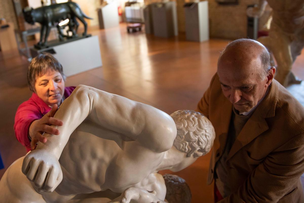 Aldo Grassini and Daniela Bottegoni touching an artwork
