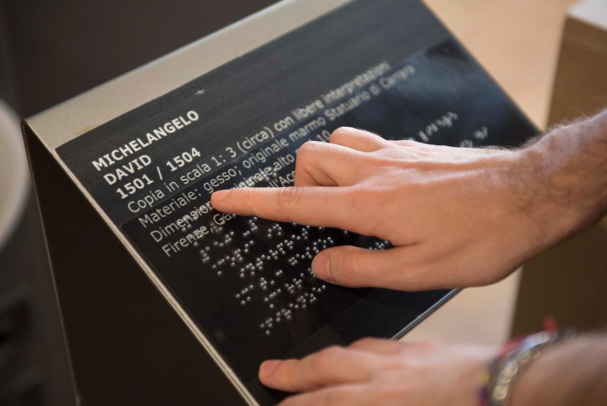 mano che tocca una targa in braille