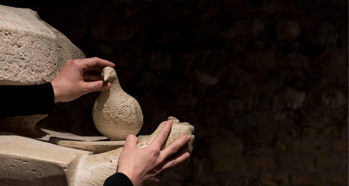 mani che toccano particolare opera originale in marmo travertino Stele delle colombe di Girolamo Ciulla